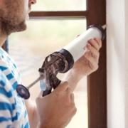 Man uses caulking gun to seal windows in apartment