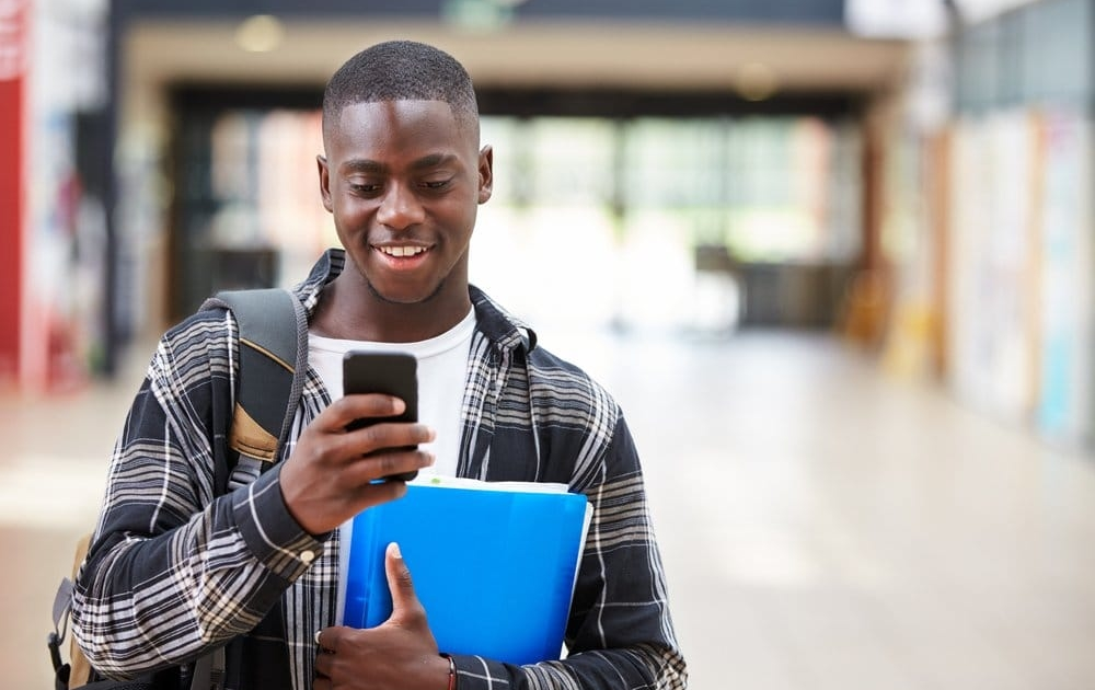 Young man uses a prepaid cell phone in college