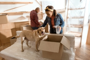 couple with moving boxes and their puppy